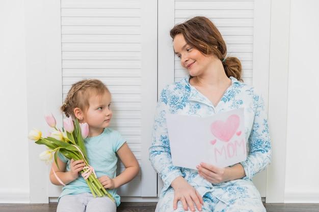 Recht kleine tochter und mutter, die einander mit dem halten der grußkarte und des bündels tulpenblumen betrachtet