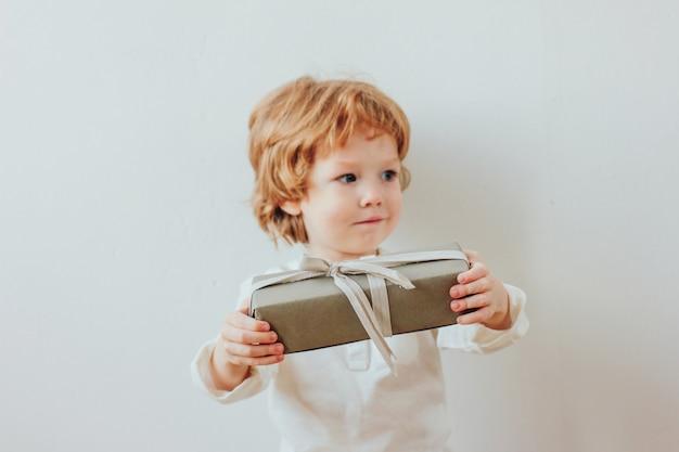Recht kleiner junge, der geschenkbox, minimalismusart hält