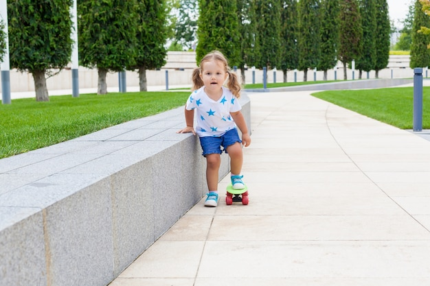 Recht kleines mädchen, das lernt, zum skateboard eiszulaufen