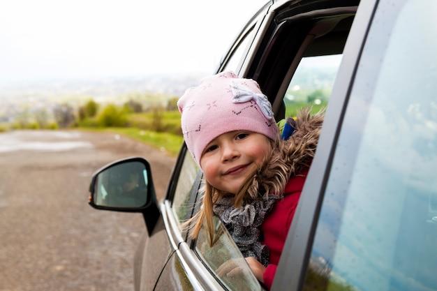 Recht kleines mädchen im auto, das durch autofenster schaut.
