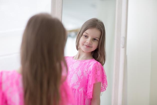 Recht kleines mädchen im rosa prinzessinkleid schaut im spiegel