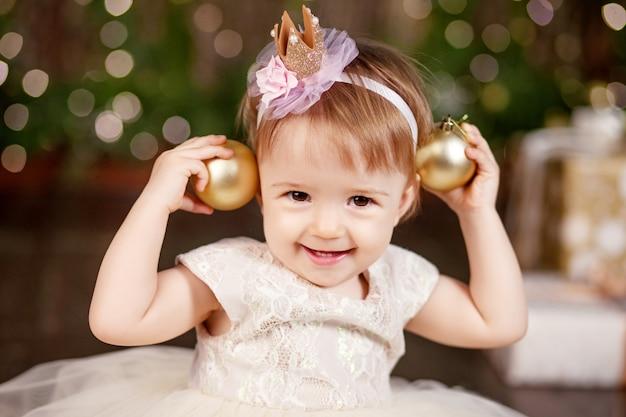 Recht kleines mädchen im weißen kleid, das über weihnachtsbaum und lichter spielt und glücklich ist. winterferien.