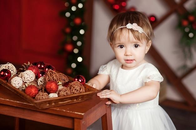 Recht kleines mädchen im weißen kleid, das über weihnachtslichter spielt und glücklich ist