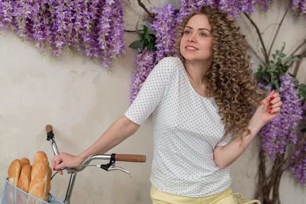 Recht lockiges mädchen lehnte sich auf ihrem fahrrad mit einem korb mit brot und seitlich träumerisch schauen - bild