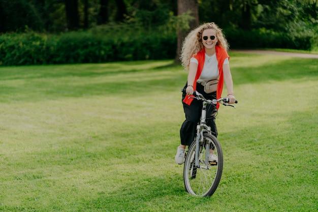 Recht nette junge frau reitet fahrrad, trägt sonnenbrille, freizeitkleidung, wirft auf grünem rasen auf