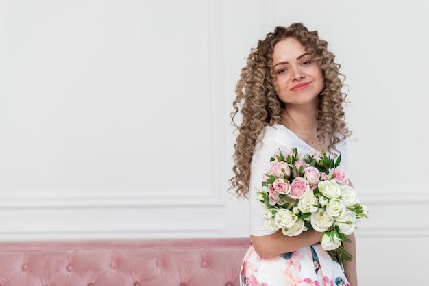 Recht romantische frau, die einen blumenblumenstrauß hält und die kamera leicht betrachtend lächelt