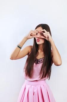Recht romantische junge indische frau, die ein herz mit ihren fingern vor ihrem kasten zeigt ihre liebe gestikulieren lässt