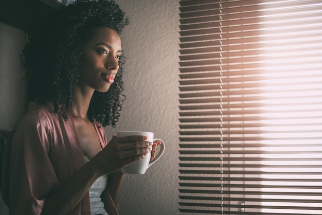 Recht schwarze frau, die am fenster mit tasse kaffee sitzt
