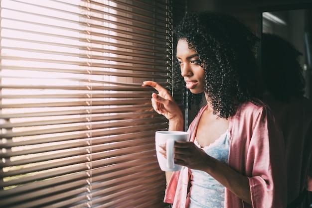 Recht schwarze frau, die am fenster mit tasse kaffee steht