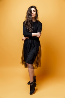 Recht sexy frau oder mädchen der junge mit nettem gesicht und dem langen brunettehaar hat modernes make-up im schwarzen kleid auf gelbem hintergrund