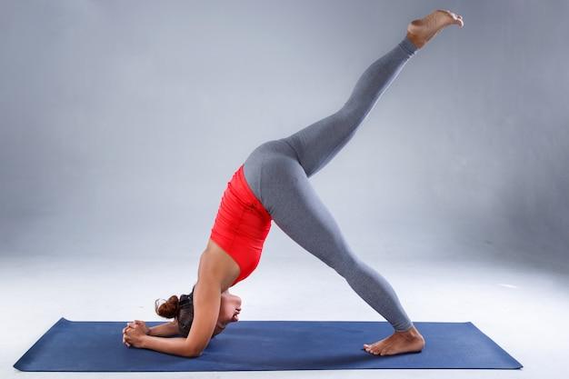 Recht sportliche indische frau, die schwierige yogahaltung übt
