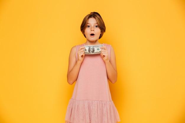Recht überraschtes mädchen, das dollar hält und die kamera lokalisiert schaut