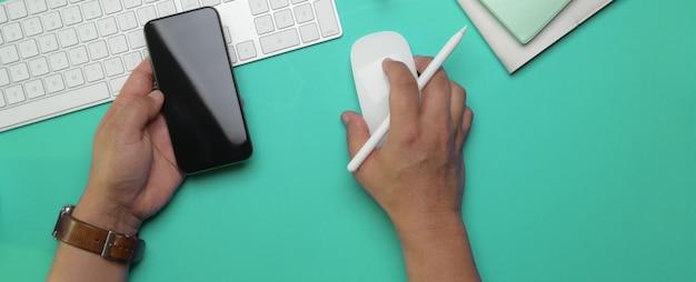 Rechte hand des männlichen unternehmers unter verwendung des computergeräts und der linken hand, die smartphone auf arbeitstisch halten