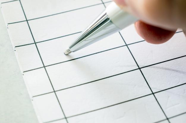 Rechte hand, die einen stift unterzeichnet auf papier hält