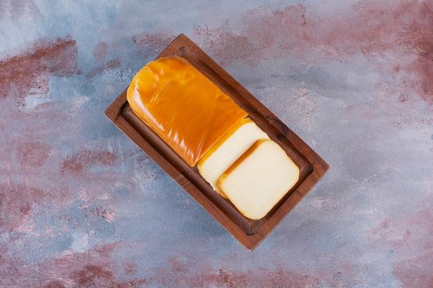 Rechteckig geschnittener käse auf einem brett auf der marmoroberfläche