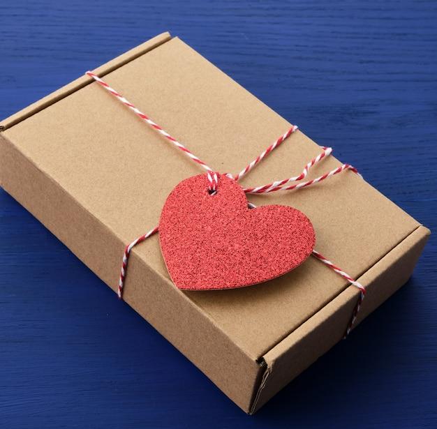 Rechteckige braune schachtel mit einem geschenk und einem roten papierherz, das an ein seil gebunden ist