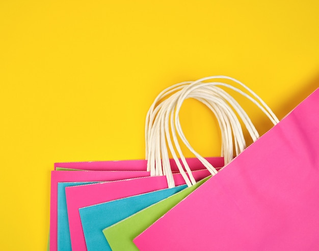 Rechteckige einkaufstüten aus buntem papier mit weißen griffen