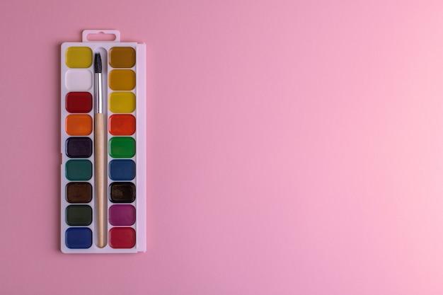 Rechteckige kastenpalette mit honigfarbenen aquarellen und einem pinsel auf einem rosa hintergrund.