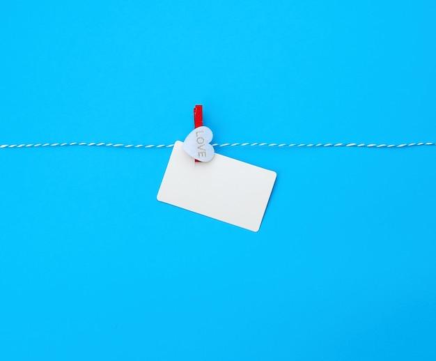 Rechteckige visitenkarte des weißen leeren papiers auf dekorativer wäscheklammer mit einem roten herzen