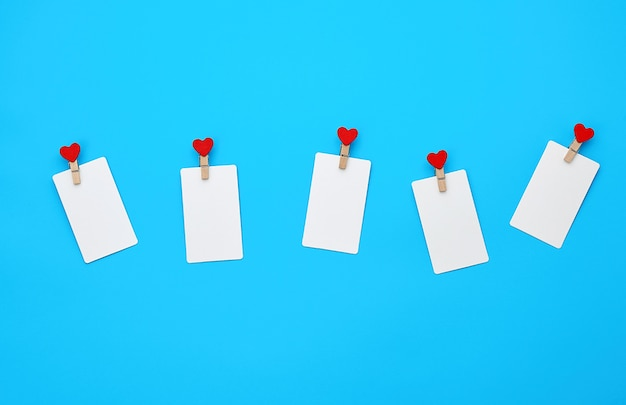 Rechteckige visitenkarten des weißen leeren papiers auf dekorativen wäscheklammern mit einem roten herzen