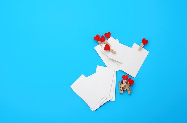 Rechteckige visitenkarten des weißen leeren papiers auf dekorativen wäscheklammern mit einer roten herzlüge