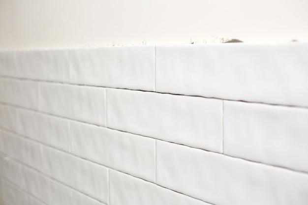 Rechteckige weiße keramikfliese an der küchenwand. reparaturen in der küche. stilvolle trendige weiße keramikfliesen. renovierung von wohnungen und bädern.