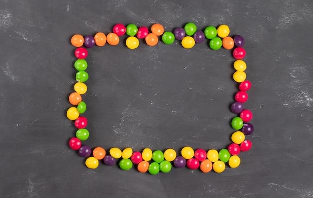 Rechteckiger rahmen aus mehrfarbigen runden bonbons