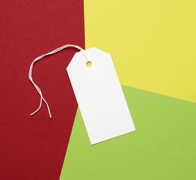 Rechteckiges etikett aus weißem papier an einem seil auf einem farbigen raum, flach gelegen