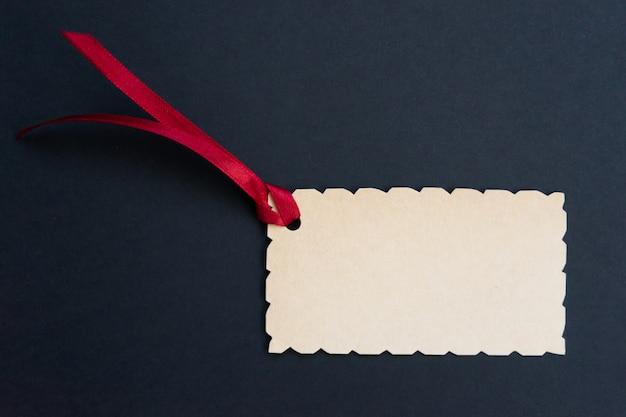 Rechteckiges etikett mit einer geschnitzten kante und einem roten band auf einer dunklen.