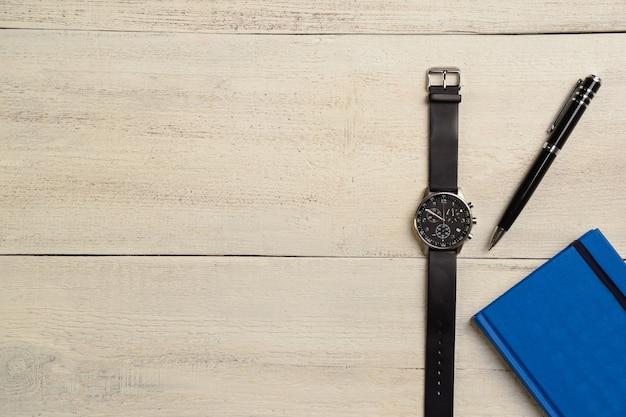 Rechts auf einem hellen holztisch liegen eine mechanische armbanduhr, ein tagebuch und ein stift