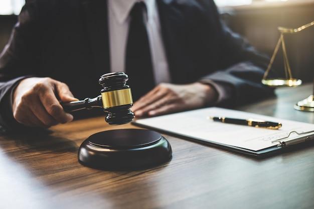 Rechtsanwalt, der an dokumenten arbeitet und hammer im gerichtssaal hält