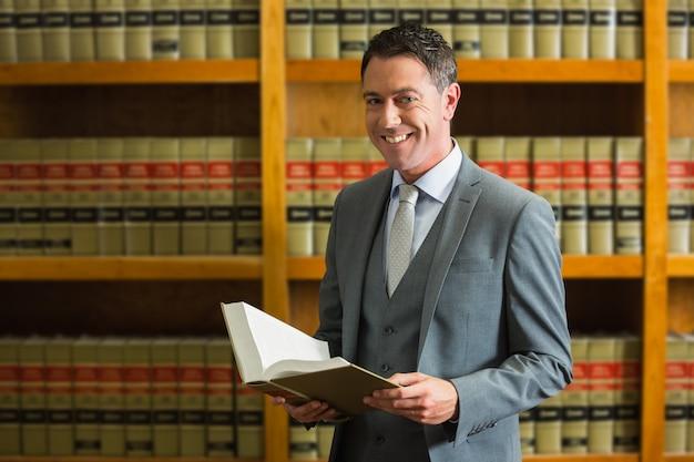 Rechtsanwalt, der buch in der gesetzesbibliothek hält