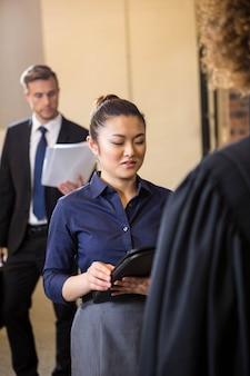 Rechtsanwalt, der dokumente betrachtet und auf geschäftsfrau im büro einwirkt