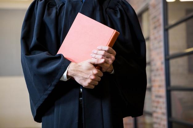 Rechtsanwalt, der ein gesetzbuch im büro hält