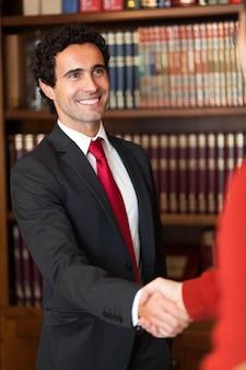 Rechtsanwalt, der hände mit einem kunden rüttelt