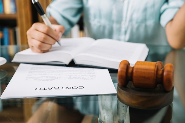 Rechtsanwalt, der mit hammer, vertrag und buch am tisch sitzt