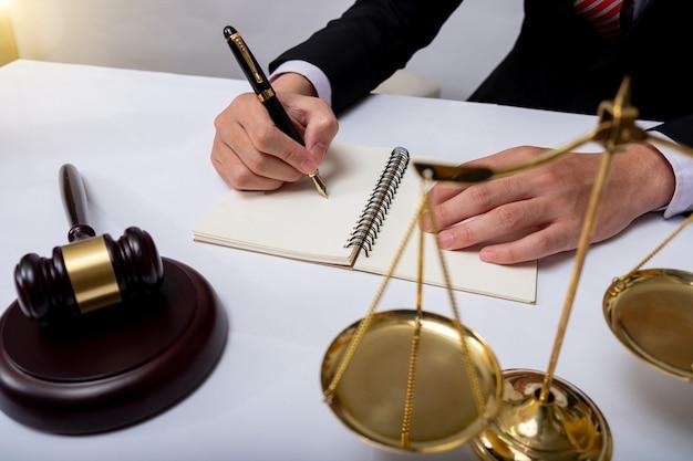Rechtsanwalt detail eines richters, der an seinem schreibtisch sitzt, neue gesetze und gesetze studiert und notizen macht. selektiver fokus.