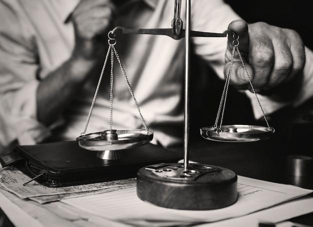 Rechtsanwalt mit skala auf dem tisch