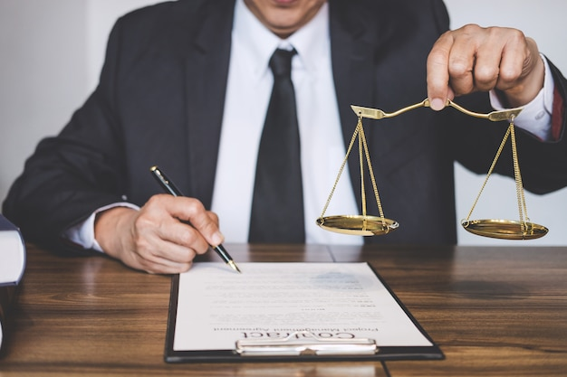 Rechtsanwalt oder berater, der an dokumenten arbeitet und balance im gerichtssaal hält