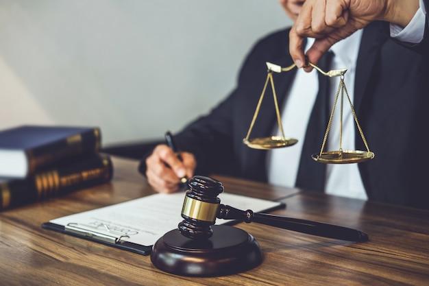 Rechtsanwalt oder berater, die an dokumenten arbeiten und balance im gerichtssaal halten