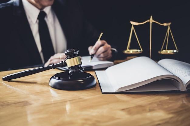 Rechtsanwalt oder richter, der mit vertragspapieren, gesetzesbüchern und hölzernem hammer auf dem tisch arbeitet
