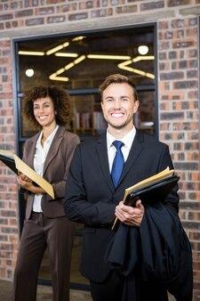 Rechtsanwalt und geschäftsfrau, die nahe bibliothek mit dokumenten im büro stehen