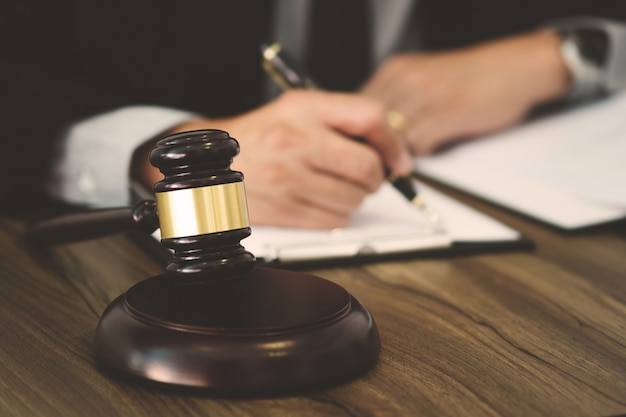 Rechtsanwalts- / richterhammer, der mit rechtsdokumenten in einem gerichtssaal arbeitet