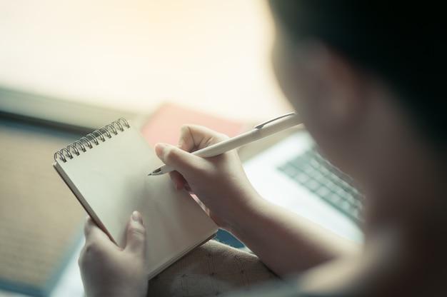Rechtshändige frau, die auf kleinen notizblock schreibt