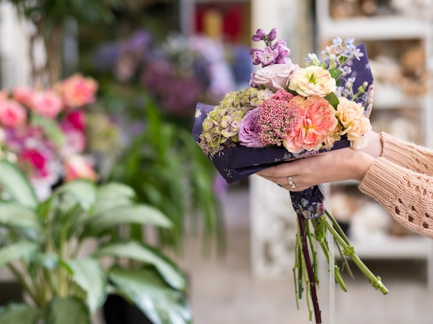 Rechtzeitige lieferung von blumensträußen für einen besonderen tag - geburtstag oder jubiläum. frauenhände, die eine kreative anordnung von rosenpfingstrosen, hortensien und fliedern halten
