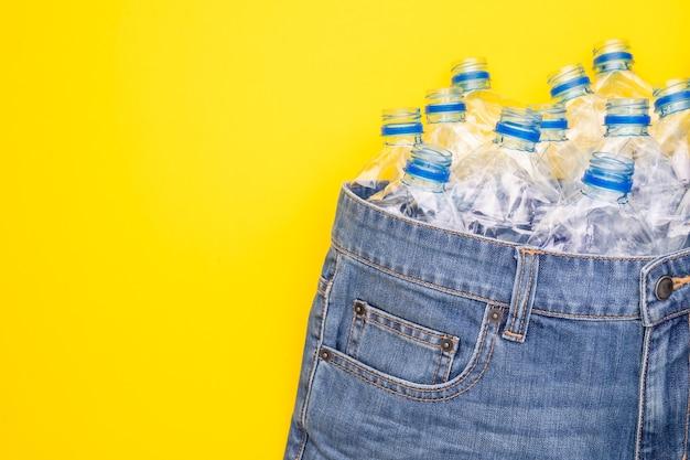 Recyceln sie die technologie der plastikflasche, um kleidung herzustellen. draufsicht alte wasserflasche und blaue kurze jeans