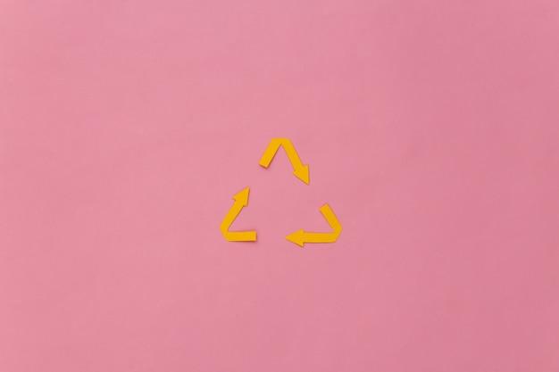 Recycelte pfeile unterzeichnen auf rosa pastellhintergrund.