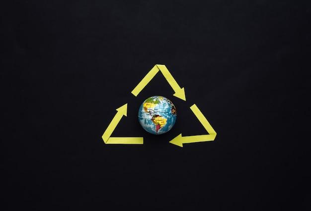 Recycelte pfeile unterzeichnen und globus auf schwarzem hintergrund. planeten retten. ansicht von oben