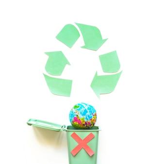 Recycle logo und globus in mülleimer