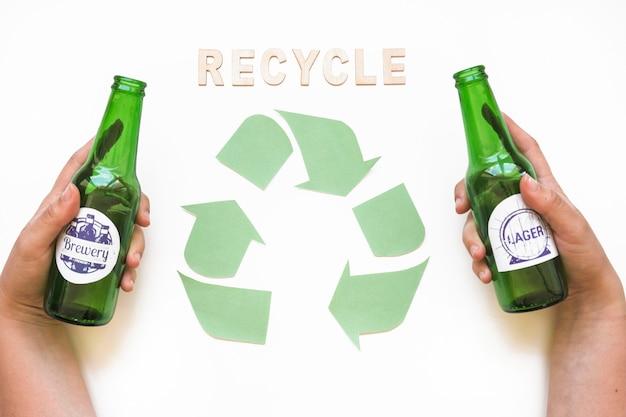 Recycle-schriftzug mit symbol und hände mit flaschen